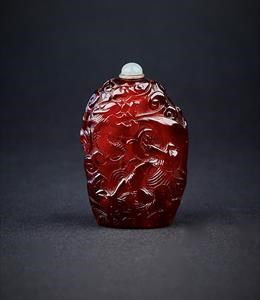 Amber, of rich transparent brown tone, very well hollowed, of natural pebble form, extensively carved with dragons above waves and in scrolling clouds, in pursuit of a flaming pearl. 1780-1850